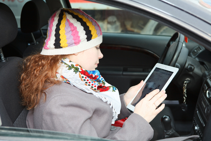 Young Caucasian woman sitting in car on passenger seat and holding an iPAD